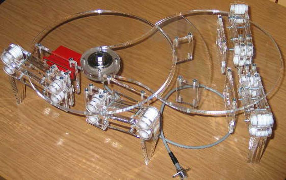 Projekt wykonywany przez: Marek KRET-Pomysł:D, część mechaniczna projektu, modele bryłowe, złożenia, symulacje, wykonanie modelu fizycznego i złożenie Marcin MUCHYŃSKI, Grzegorz MUCHA-część elektroniczna przedsięwzięcia, sterownik mikroprocesorowy (pierwotnie AtMEGA2560, aktualnie ARM9), serwonapędy wykonawcze, oprogramowanie układu sterowania  Opiekunem naukowym projektu jest dr inż Jan BIS